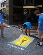 Social media caddies from Ponte Vedra High School's Marketing Academy work on a downtown promotion for The Players along West Adams Street.