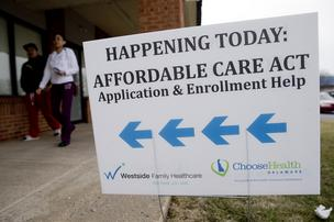 An Affordable Care Act application and enrollment help sign stands outside a Westside Family Healthcare center in Bear, Delaware, U.S., on Thursday, March 27, 2014. Six million Americans have signed up for private health plans under Obamacare, President Barack Obama said, a symbolic milestone for a government that has struggled to get the law off the ground.