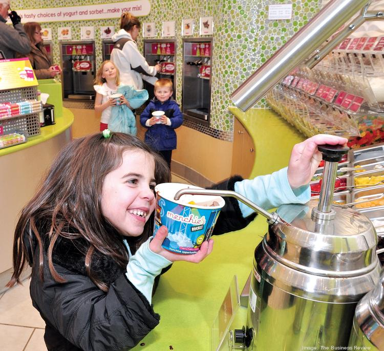 A Menchie's customer in New York loads up a dish of frozen yogurt.