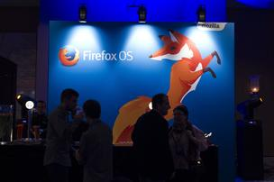 Attendees pass a Firefox operating system logo during a Mozilla Corp. news conference ahead of the Mobile World Congress in Barcelona, Spain.