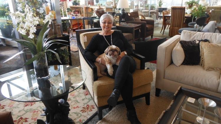 Estate Interiors owner Karen Douglas, with Molly, sits among high-end consignment items in her Bellevue store. The items which come from the wealthiest ZIP codes in the region.