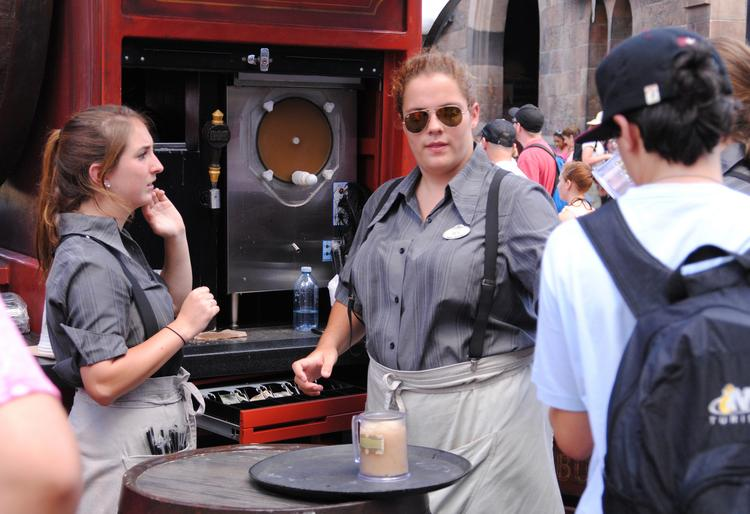 Vendors at the Butterbeer stand assist guests at Wizarding World of Harry Potter.