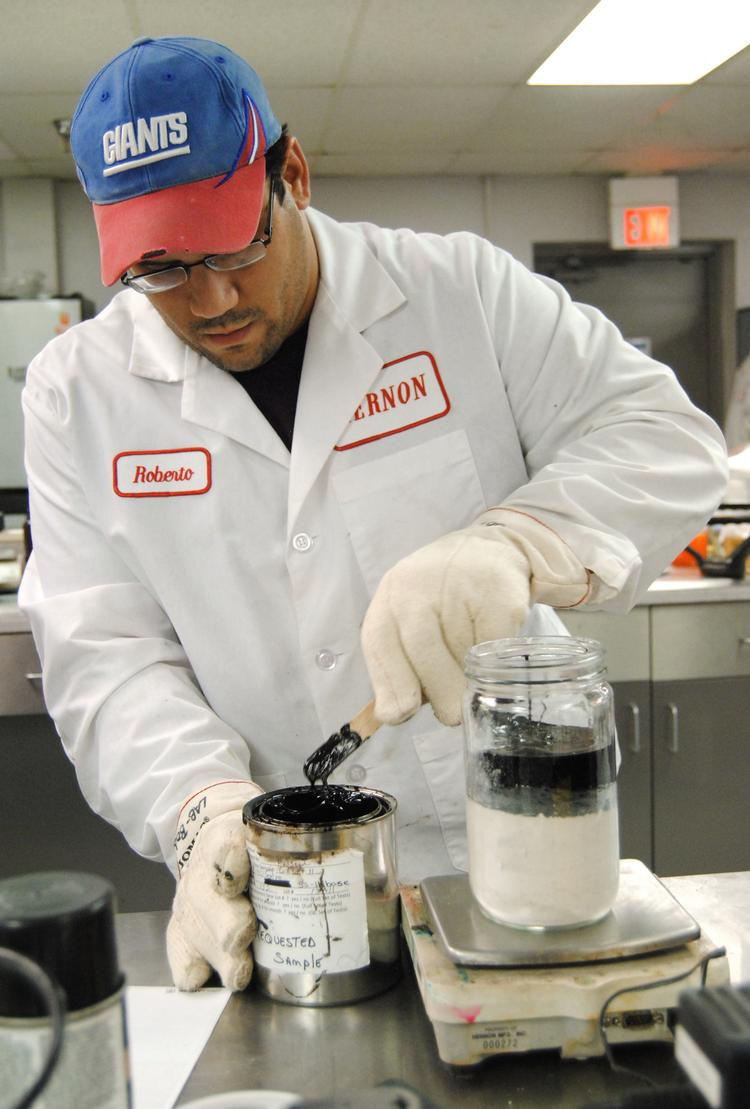 Hernon Manufacturing quality and development specialist Roberto Rivera mixes a sample of adhesive for testing.