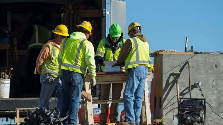 Kiewit employees work on the Paseo/I-25 project. New employees wear bright green hard hats for the first 30 days on the job while they complete extensive training in safety procedures and hazard recognition.