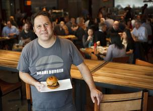 Umami Burger founder Adam Fleischman holds a plate with an Umami Burger made with shiitake mushrooms, caramelized onions, roasted tomato, parmesan crisp, and umami ketchup while posing for a portrait during lunch at  UMAMIcatessen in Los Angeles 2012.