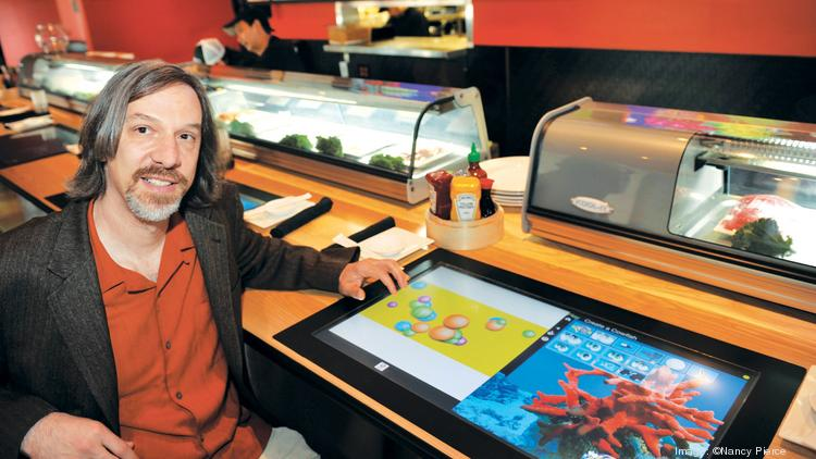 Mike Feldman, president of T1Visions, shows off a touch screen installed at Cowfish.