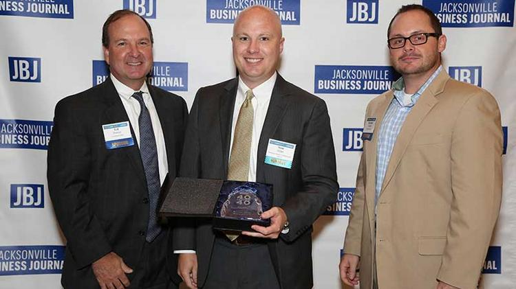 40 Under 40 winner Scot Elder of Medtronic Surgical Technologies stands between Gil Pomar and Jonathan Tucker.
