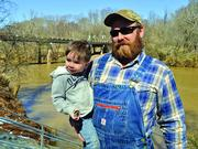 Eden native Benjamin Adkins holds his son on the banks of the Dan River.
