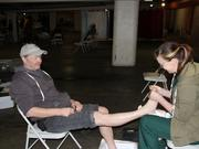 A man receives foot care from an OHSU medical student volunteer at the 2013 Health Care Equity Week health screening fair.
