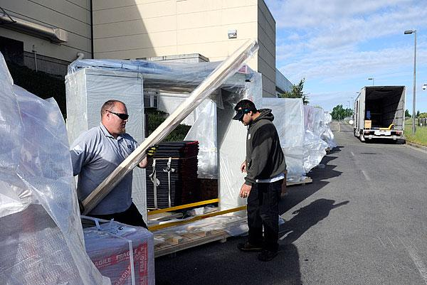 Dane Holland, left, and Jonathan Marcoux unload new equipment at TSI, which is expanding its semiconductor manufacturing effort.