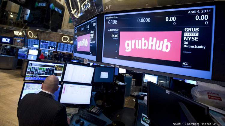 A trader works under a monitor displaying the GrubHub Inc. logo inside the New York Stock Exchange.
