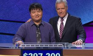 Arthur Chu and Alex Trebek pose in front of the total amount of the contenstant's winnings: $297,200.