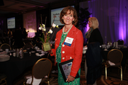 Diana Marsden of Aries Apparel holds her Orchid Award at the Women of Influence luncheon.