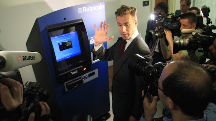 CEO and co-founder of Robocoin, Jordan Kelly prepares to insert his hand in the machine so his palm print can be read. On Thursday, a Robocoin bitcoin ATM became available for people to use in Seattle.