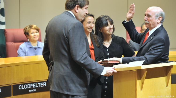 Dan Clodfelter (right) was sworn in Wednesday as mayor of Charlotte. The oath was administered by state Sen. Fletcher Hartsell Jr. (R-Cabarrus). Standing with the new mayor were his daughter, Catherine Clodfelter, and his wife, Elizabeth Bevan.