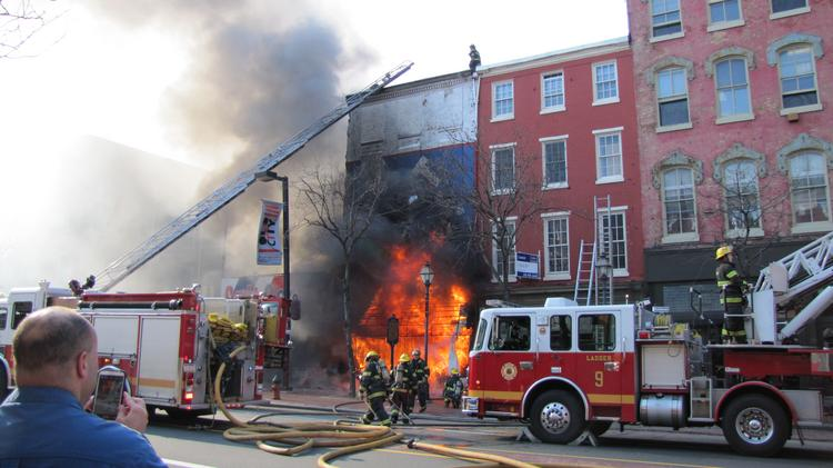 Flames shoot out of 304 Market St., one of two Suit Corner buildings engulfed in flames.