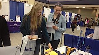 Kiley Voss, 16, at left, and Carly Rachwal, 16, both juniors at Orchard Park High School, stop Wednesday at the Allegany College booth at the Buffalo National College Fair. The two-day event took place at the Buffalo Niagara Convention Center.