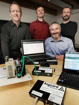 David Mattes, bottom right, founder of Asguard Networks, displays some of the  company's industrial security systems. He's joined by colleagues, from left, Curtis Vredenburg, Ludwin Fuchs and Eric Artzt at their office in Seattle's Fremont neighborhoon. Mattes is concerned that the newly revealed Heartbleed bug could affect industrial infrastructure such as power plants.
