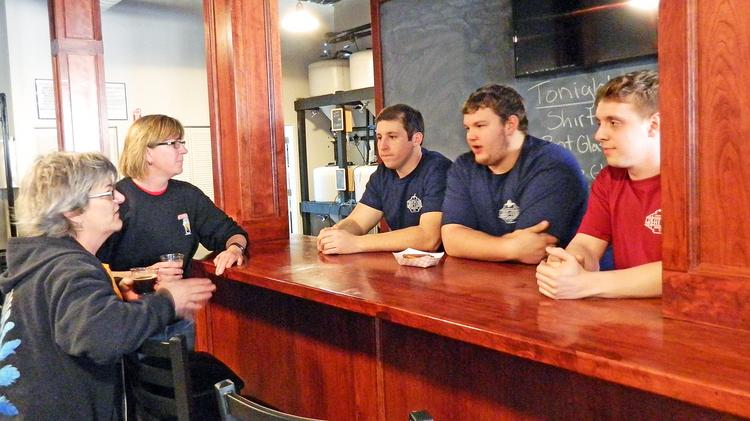 Behind the bar, Great Flood co-owners Vince Cain, Matt Fuller and Zach Barnes chat with Leah Dienes and Denise Szostak of Apocalypse Brew Works.