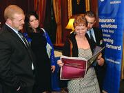 Winner Erika Arbogast of Blind & Vision Rehabilitation Services of Pittsburgh looks over her profile in the supplement.