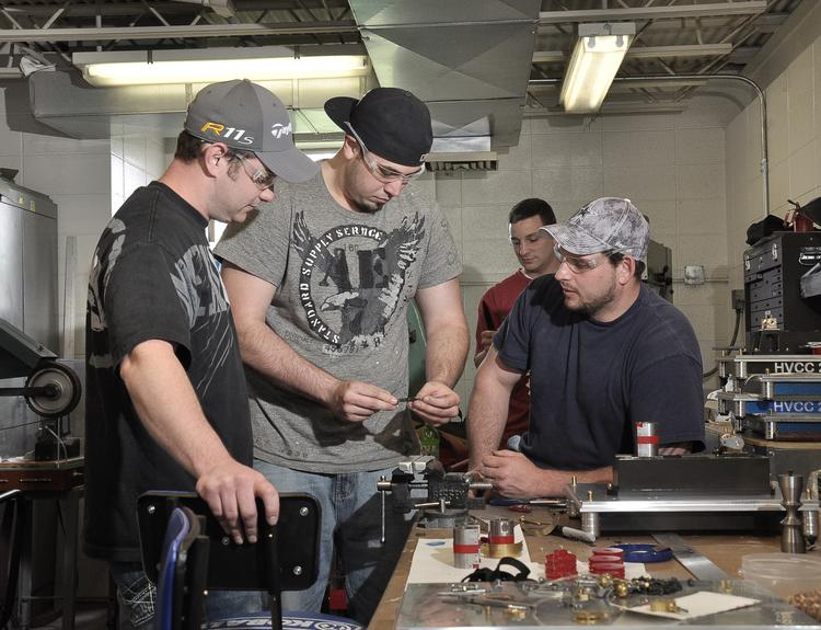 Brian Gardy, Scott Mielewski and Matthew Muttarkey assemble a steam engine at HVCC's manufacturing for technical systems class in April 2012.
