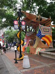 A stage made out of yarn sits on the perimeter of Hemming Plaza facing North Laura Street.