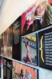 A memorable moments wall has pictures and text commemorating athletic achievements and milestones in women's sports.