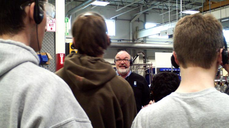 Rick Steinke, vice president of manufacturing for Sentry Equipment Corp. in Oconomowoc, talks to students from Kettle Moraine High School as part of the Schools2Skills program.