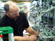 Dan Stoltz, an assembly worker at Sentry Equipment Corp., puts together an electrical assembly as a group of students toured the company.