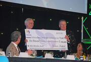 """James Graham Brown Cancer Center director Dr. Don Miller, left, accepted a ceremonial check from Robert """"Rip"""" Hatfield, who is chairman of the Kentucky Derby Festival Foundation."""