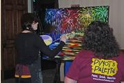 Lindsay Cahill, an artist from Pinot's Palette in St. Matthews, painted another piece of art that will be auctioned off to support the Kentucky Dervy Festival Foundation. Watching is Martha Noe.