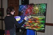 Lindsay Cahill, an artist from Pinot's Palette in St. Matthews, put more finishing touches on the painting as she considered whether she should add more fireworks to signify Thunder Over Louisville.