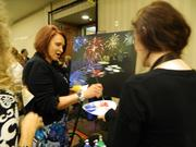 Durenda Dolan, manager of sterile processing for Norton Healthcare Inc., takes a few minutes to try her hand at painting a fireworks scene outside the They're Off! Luncheon. Assisting her is Lindsay Cahill of Pinot's Palette.