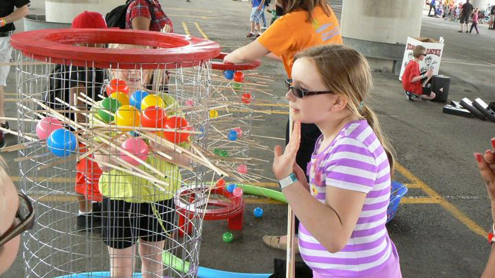 Grace Pate, 10, of Carmel, Ind., studies how to remove sticks during a game at Saturday's ThunderBlast at the Kentucky Science Center.