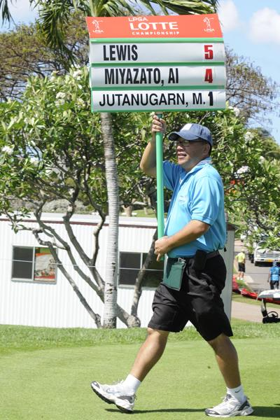 A volunteer for the 2013 LPGA LOTTE Championship carries the sign for the players at the first tee.