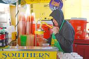 Kevin Tourney, a worker at Go Greek, was bundled up as he made lemonade early on Saturday while temperatures were still cool. He expected sales to pick up as the weather warmed.