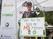 Audrey Blank, an MS ambassador and Team BP partner, greets BP MS 150 cyclists from the finish line in Austin while holding a sign thanking the riders for their efforts and fundraising.