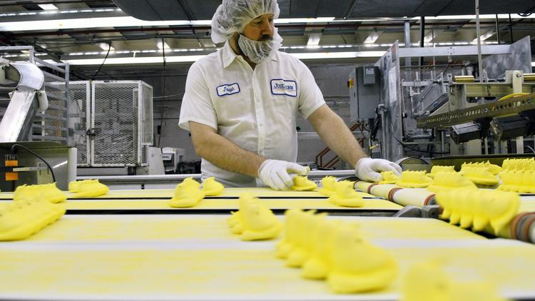 Joseph Kovacevic performs quality control as Marshmallow candy Peeps chicks move down a conveyor belt inside the Just Born Inc. manufacturing facility in Bethlehem, Penn.