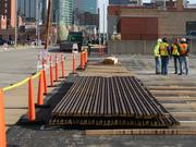 Crews unloaded the first delivery of streetcar rail Wednesday into a parking lot east of the Corrigan Building – one of two staging areas.
