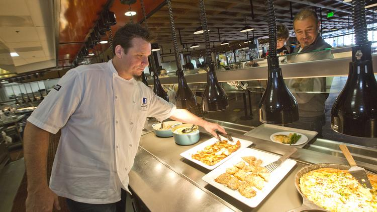 Facebook Executive Chef Dean Spinks adjusts lunch entrees served up for a recent breakfast-for-lunch theme, which included fare like maple-apple bacon french toast.