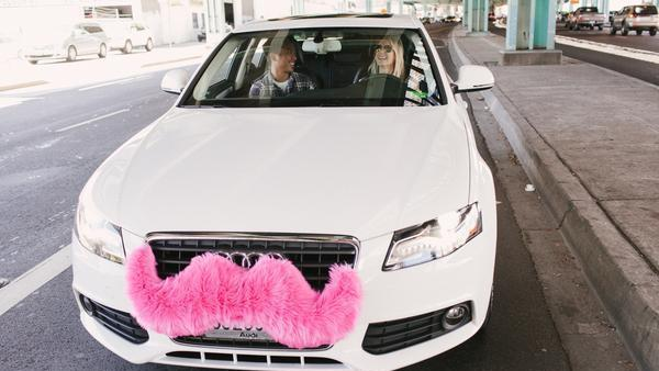 Lyft drivers attach pink mustaches to the front grilles of their cars.