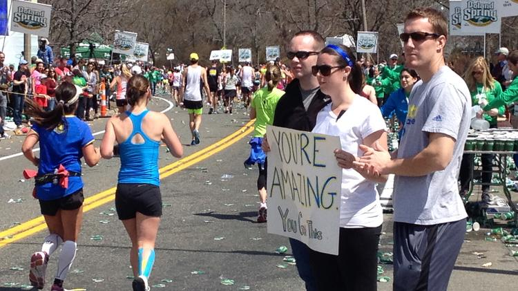 Supporting runners along the route is what the Boston Marathon is all about. From left, Craig Duffy of Franklin, Caroline O'Malley of newton and John Robinson Rockport show their sign of support.