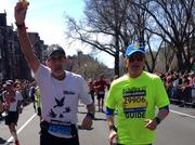Bob Cremin, right, ran the 2014 Boston Marathon as a guide for Achilles International, a nonprofit that provides a community of support to disabled runners. Here he helps a runner from South Carolina, named Richard, who kept getting leg cramps and needed support.