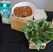 Almonds, basil and soy milk are ready to combine in a blueberry, basil, almond milk smoothie.