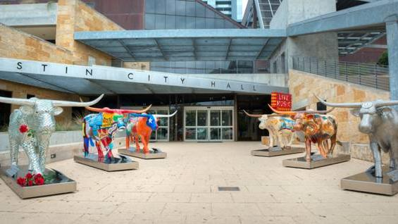 A small herd of artistically decorated Longhorn sculptures are seen outside of Austin City Hall. The fiberglass cattle are being auctioned this week at a charity fundraising event held by the Mack, Jack & McConaughey group. Click on the image to take a photographic tour of the bovine-based art installations.
