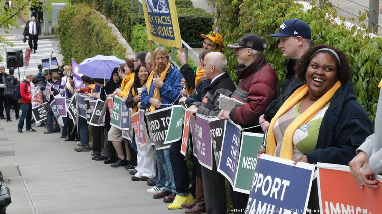 Supporters of the $15 minimum wage made a human ring around Seattle City Hall on Wednesday.  The rally is the day before Mayor Ed Murray has scheduled a press conference on raising the minimum wage.