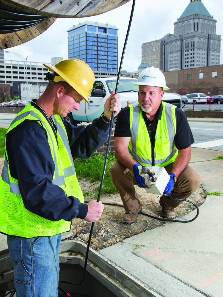 North State Communications workers Scotty Rhodes (left) and Sandy Weavil run fiber optic cable in downtown Greensboro.