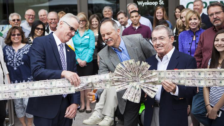 Glen Jammaron, vice chairman and president of Alpine Bank, cuts a ribbon of $5 bills to celebrate the bank's branch opening in LoDo April 12. To his left is Norm Franke, regional president of Alpine Bank, and on his right is Bob Young, chairman and founder of Alpine Bank.