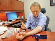 """Randy Curtis self administers a Bayer HealthCare hemophilia drug in his Oakland office. He does this ahead of """"bleeding events"""" at a cost of $1,000 every four days."""