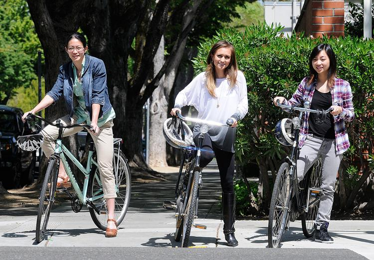 Lionakis employees — from left, Amy Leong, Rebecca Reynoso and Tela Cheang — take a spin on the commuter bikes provided by the architecture firm.